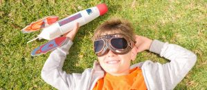 Child lying on grass with a toy rocket in hand and flight goggles on their face