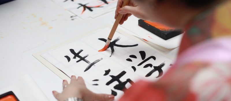 Back of person using a brush to write kanji and hiragana on a sheet of paper