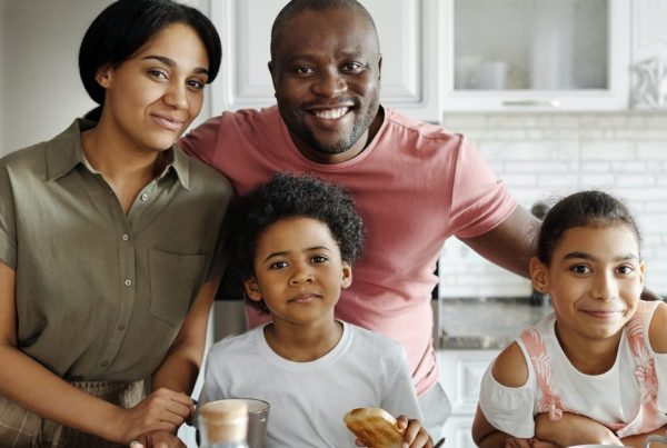 Four members of one family smiling inside of a kitchen; a mother and father in the rear, and a young son and daughter in the front