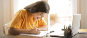 Girl in yellow shirt writing on paper in sunlight