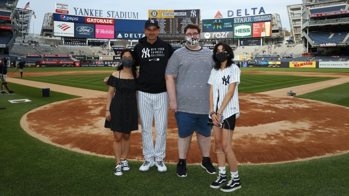 Three Yankees-Stonewall winners standing with Yankees manager, Aaron Boone, at homeplate at Yankee Stadium