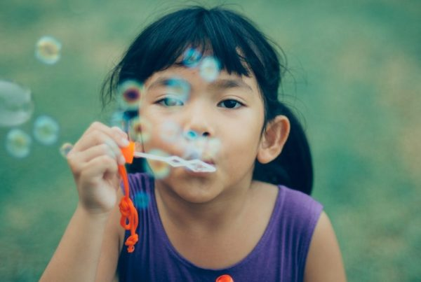Close up, eye-level shot of a young girl blowing bubbles
