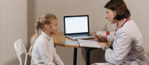 Side view of a nurse speaking with a young girl. Nurse is taking notes.