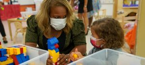 Chancellor Meisha Porter talking to a pre-k student while they play with LEGO bricks