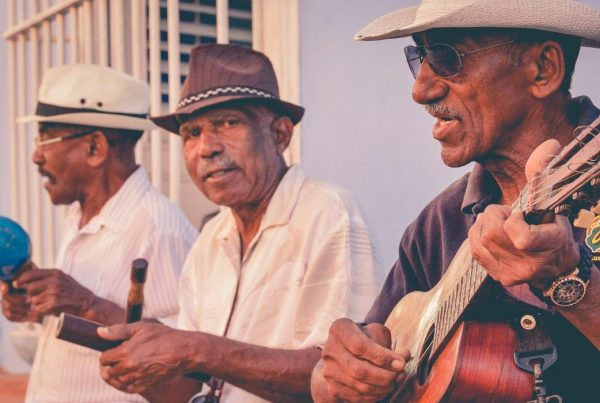 Three older men sitting in a row playing music with maracas, a conga, and a guitar.