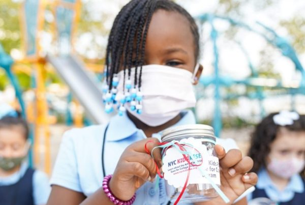 """Girl holding a mason jar that says """"NYC Kids RISE"""" while inside an outdoor school playground"""