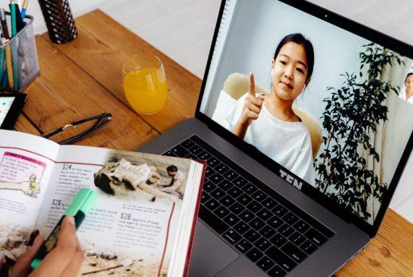 Teacher (offscreen) having a videoconference with a girl via a laptop