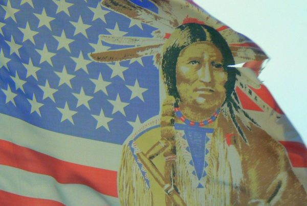 Image of an American flag with a Native American man in headdress drawn on top of it