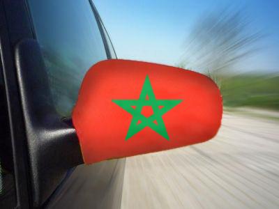 Een marokkaanse vlag over een zijspiegel van een auto