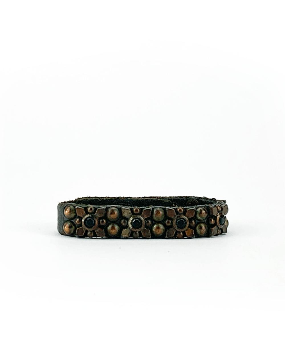 Bracciale in cuoio di toro lavorato a mano con accessori in metallo ossidato e pietre nere.