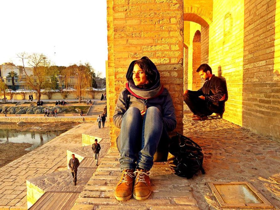 junge Frau sitzt im Abendlicht auf der Khaju-Brücke, Isfahan