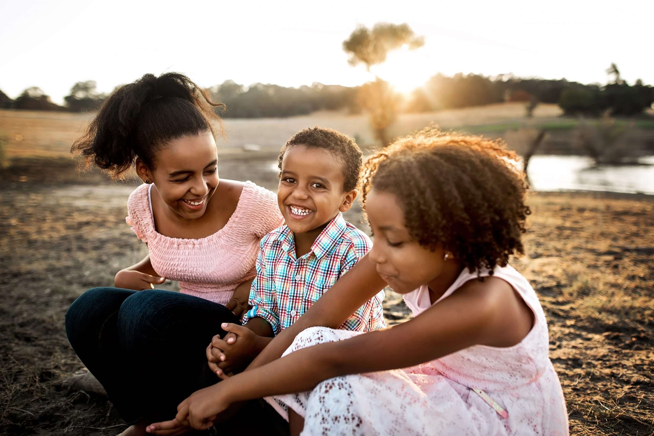 three siblings laughing together on a log at the lake during sunset