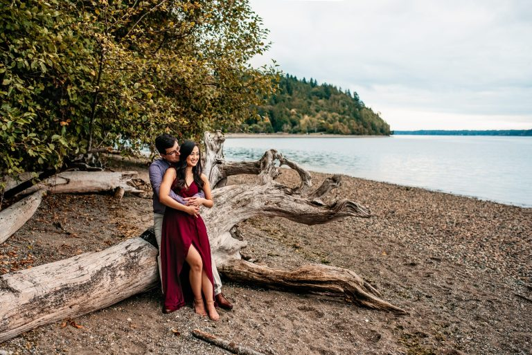engaged couple on a beach in the peninsula of Gig Harbor a dress and suit for engagement pictures