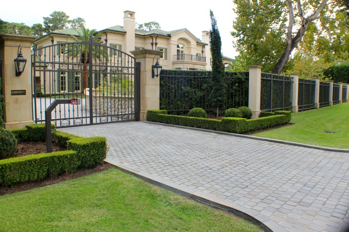 Property entrance with manicured boxwood hedges, Italian cypress and Palisades Zoysia grass. All boxwoods on the property are pruned by hand using a string line and bubble level to achieve a consistent, flawless shape.