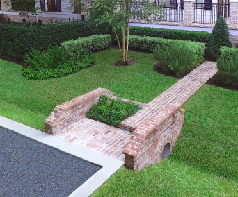 If people are going to walk there, design a path! We designed and implemented the master landscape plan for this residence in Garden Oaks where street parking is common. The gravel parking pad was constructed along the street for guests and this custom brick culvert was the perfect solution to provide an elegant way to direct visitors to the front door!