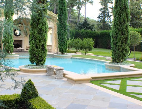 """View from the pool shows the golf area surrounded by a Cedar """"curtain"""" which must be trimmed regularly to allow sunlight to reach the edges of the putting greens."""