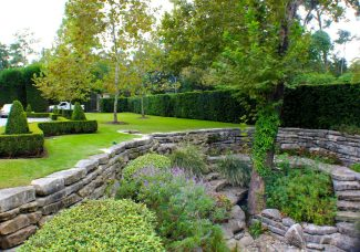 View from the bridge shows another angle of the landscaped dry creek bed as well as boxwood detailing and a privacy wall of Japanese Yews following the fence line.
