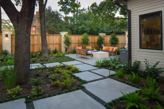 Series of stepping pads lead to the outdoor seating area and glass fire pit. Foxtail and boston ferns give the landscape a woodland feel.