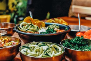4 cooking bowls filled with vegetables and other vegan foods