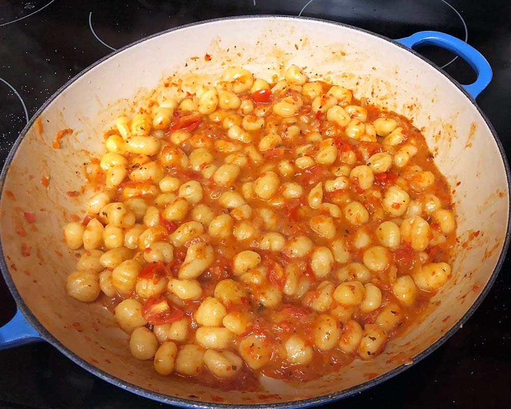 Gnocchi with roasted red pepper sauce in a skillet