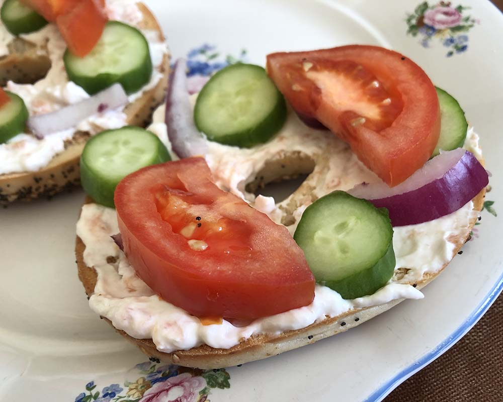 smoked salmon dip on a bagel with tomato, cucumber, and red onion