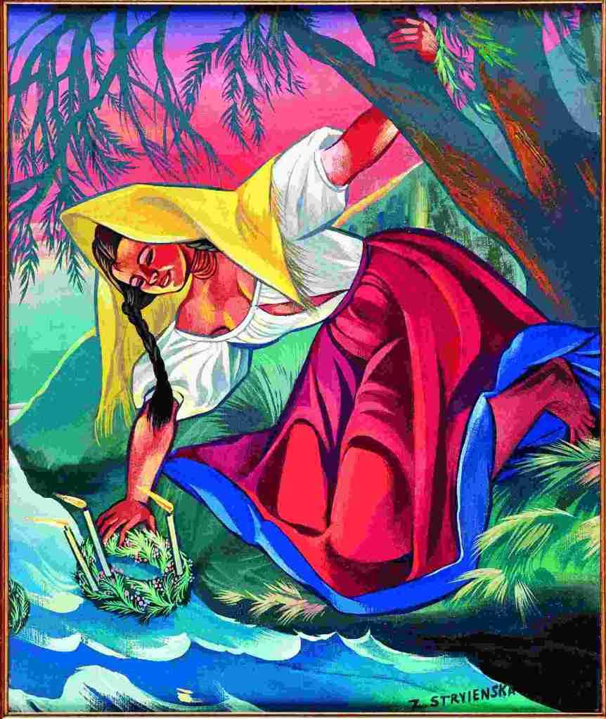 Fotografia Dariusza Kobylańskiego przedstawiająca obraz Zofii Stryjeńskiej. Wielobarwny obraz w żywych kolorach. Przedstawia kobietę z zaplecionymi długimi warkoczami. Jet ubrana w białą koszulę i długą karminową spódnicę. Jest bosa, a na głowę ma zarzuconą żółtą chustę. Kobieta pochyla się nad strumieniem. Jedną ręką wkłada do strumienia rzeki wianek z zapalonymi świecami. Drugą ręką przytrzymuje się drzewa.
