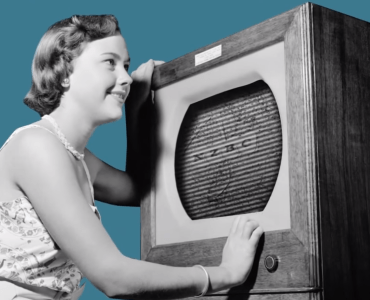 women from the 1940s holding her ear to old radio.