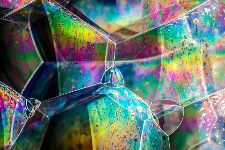 Colour photograph showing the light interference patterns and colours in soap bubble structures. This image is from the 'Colour Clouds' 2018 series by artist and photographer Kym Cox.