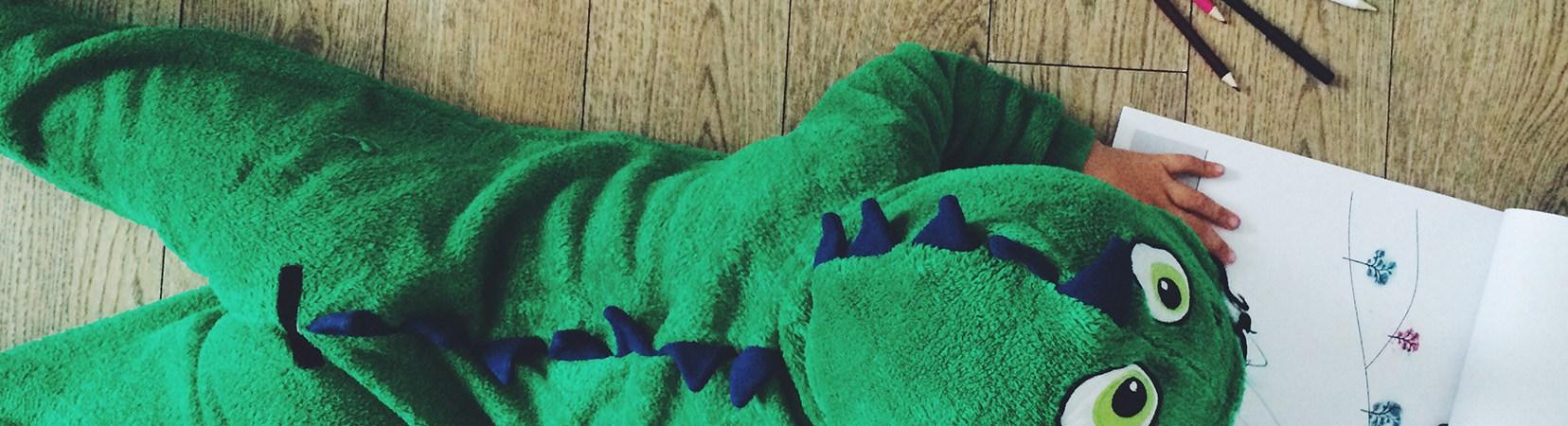 child in dinosaur onesie colouring in