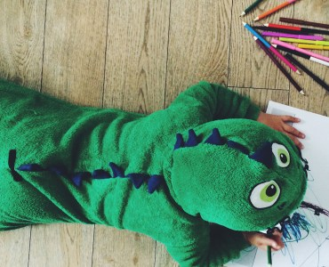 child in dinosaur onesie colouring in