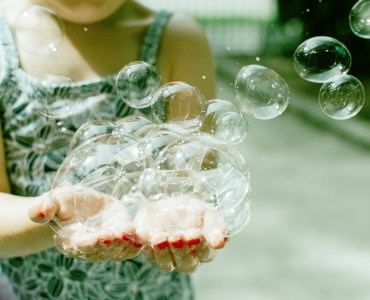 girl holding a handful of bubbles
