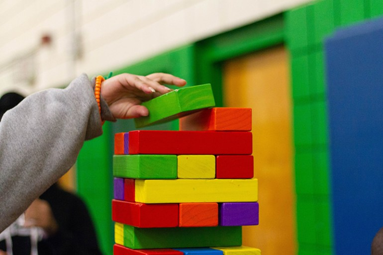 child stacking rainbow colourful wooden blocks