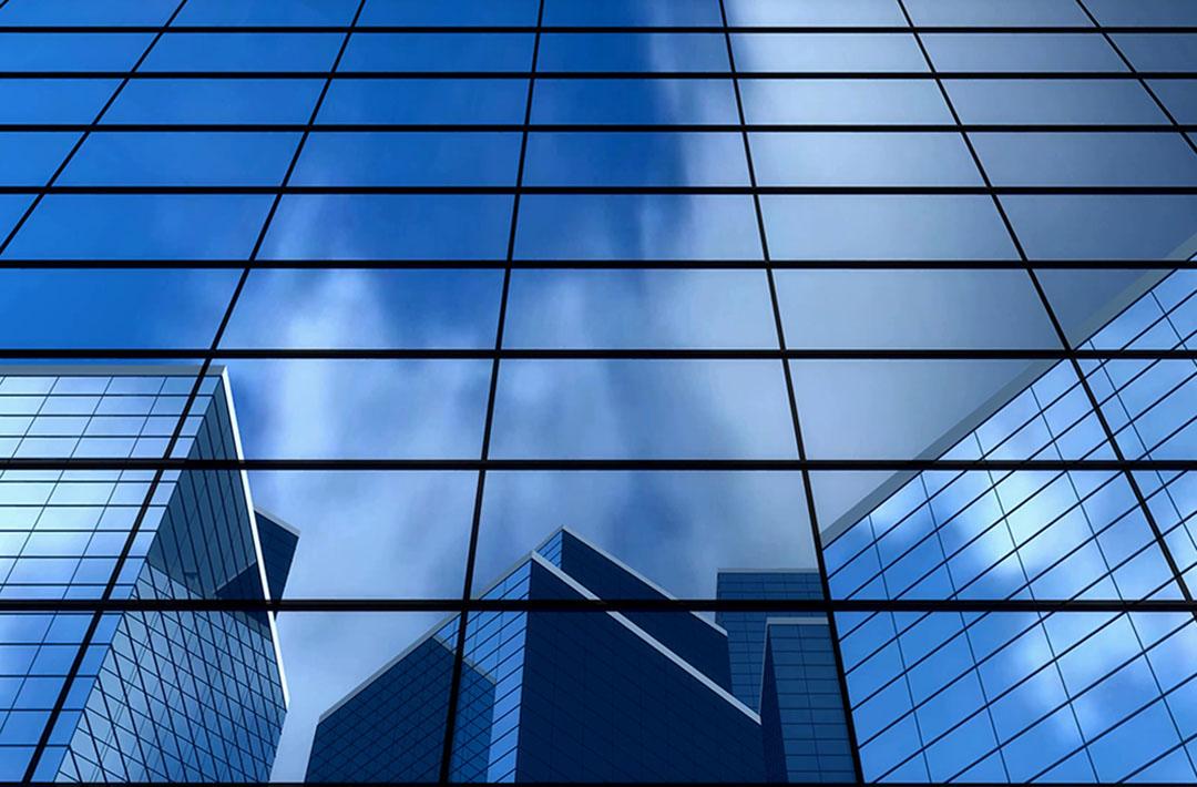 Photo graphique d'un immeuble de verre reflétant le ciel et d'autres immeubles de verre - référence