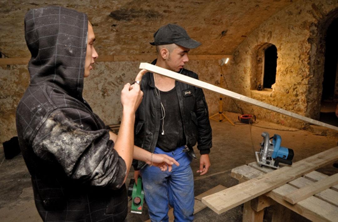 Photo de deux jeunes hommes en tenue de travail sur un chantier - référence