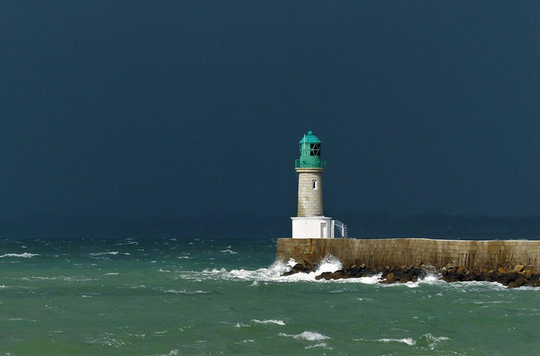 Photo d'un phare au bout d'une jetée entourée d'une mer agitée et d'un ciel chargé - référence