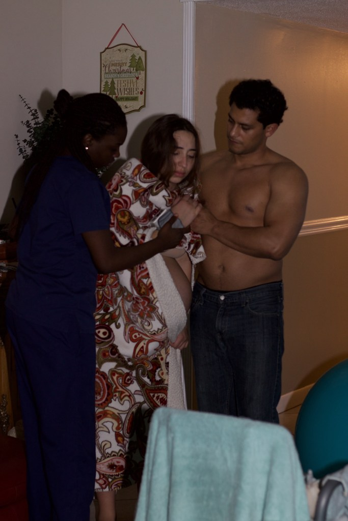 pregnant woman in labor standing with husband and midwife