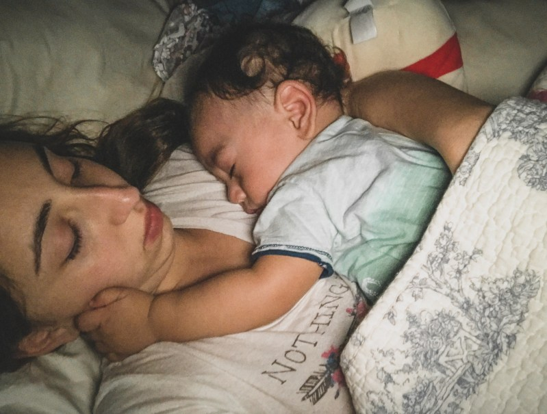 baby hugging mother while sleeping