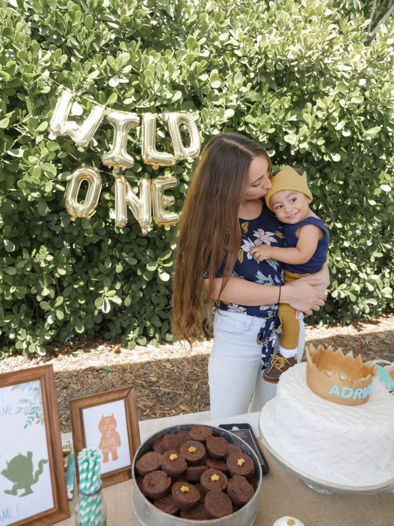 mother kissing baby at first birthday party