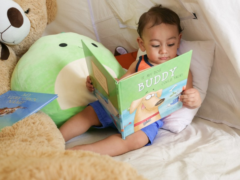 baby reading book sitting down