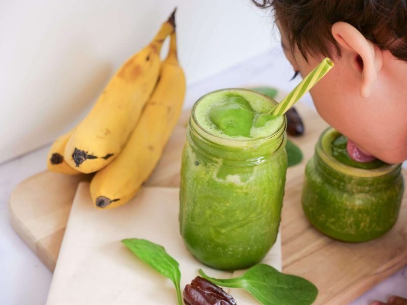 kid licking green smoothie