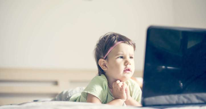 little girl watching cartoons at laptop