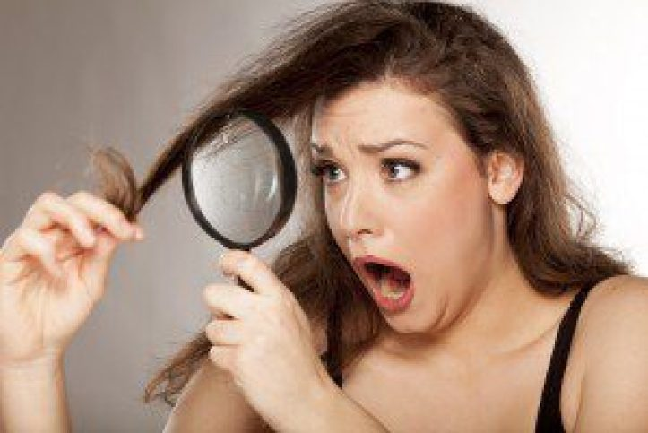 young woman looks at the tops of her hair with a magnifyier