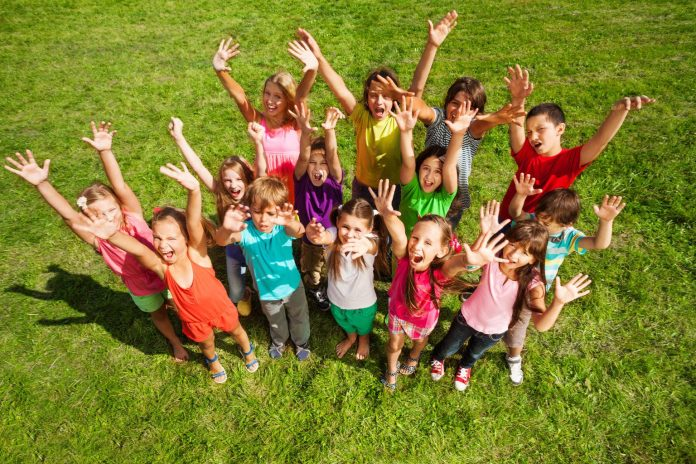Large group of happy kids, boys and girls, with lifted hands about 10 years old standing on the green grass top view