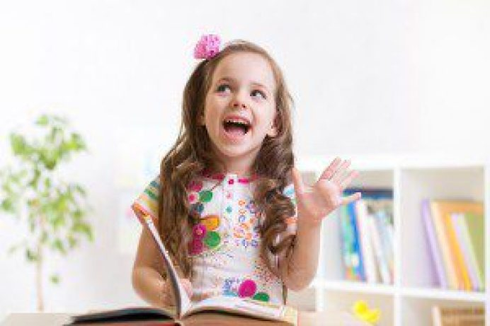 cute smiling child girl reading book at home