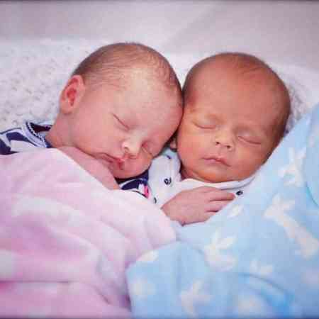 Two newborn twin babies huddled up in blankets whilst sleeping