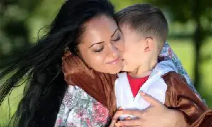 Mum cuddling her son in an embrace