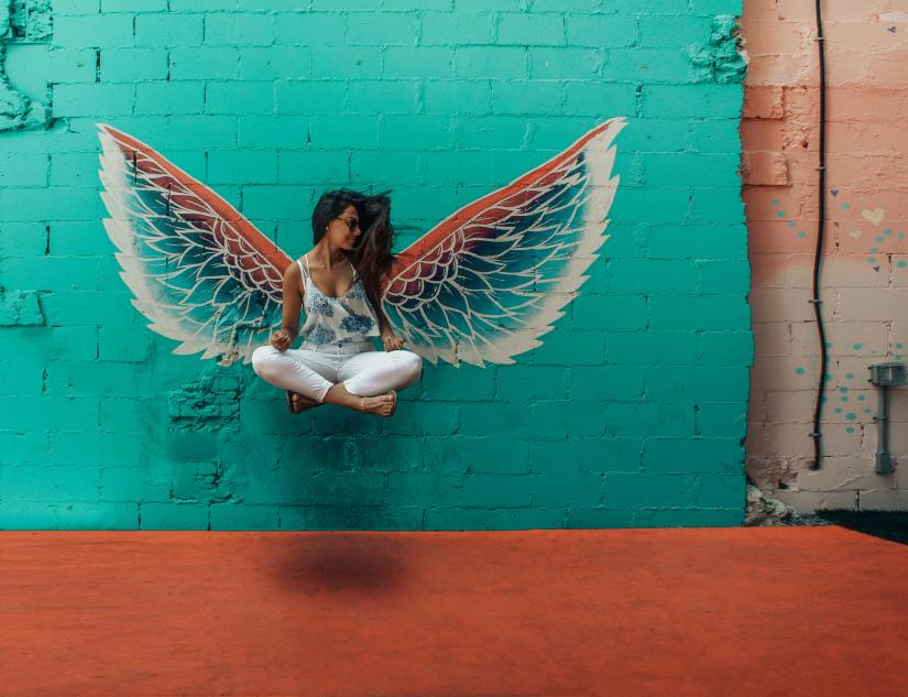 Image of carefree woman floating in meditation pose with wings drawn in graffiti on the wall behind her
