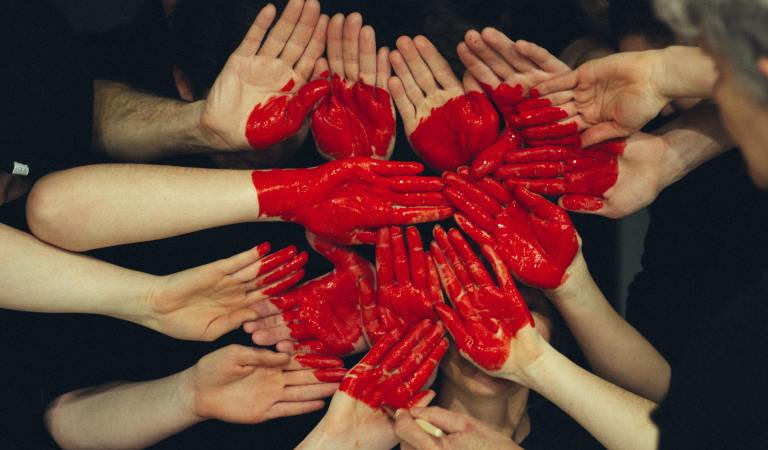 Teens in self harm group therapy join hands covered in red paint during an exercise