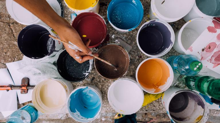 A hand dips a paintbrush into multi-colored jars of paint. Painting is one creative outlet that can be a great alternative to self harm.