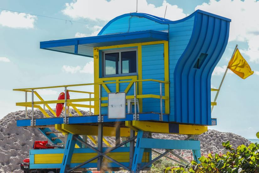 A brightly colored life guard station sits in  front of a sand dune at the beach.